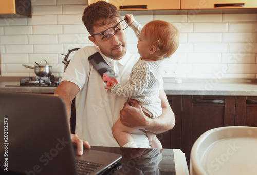 Photo Multitasking Father Working From Home On Laptop With Baby daughter