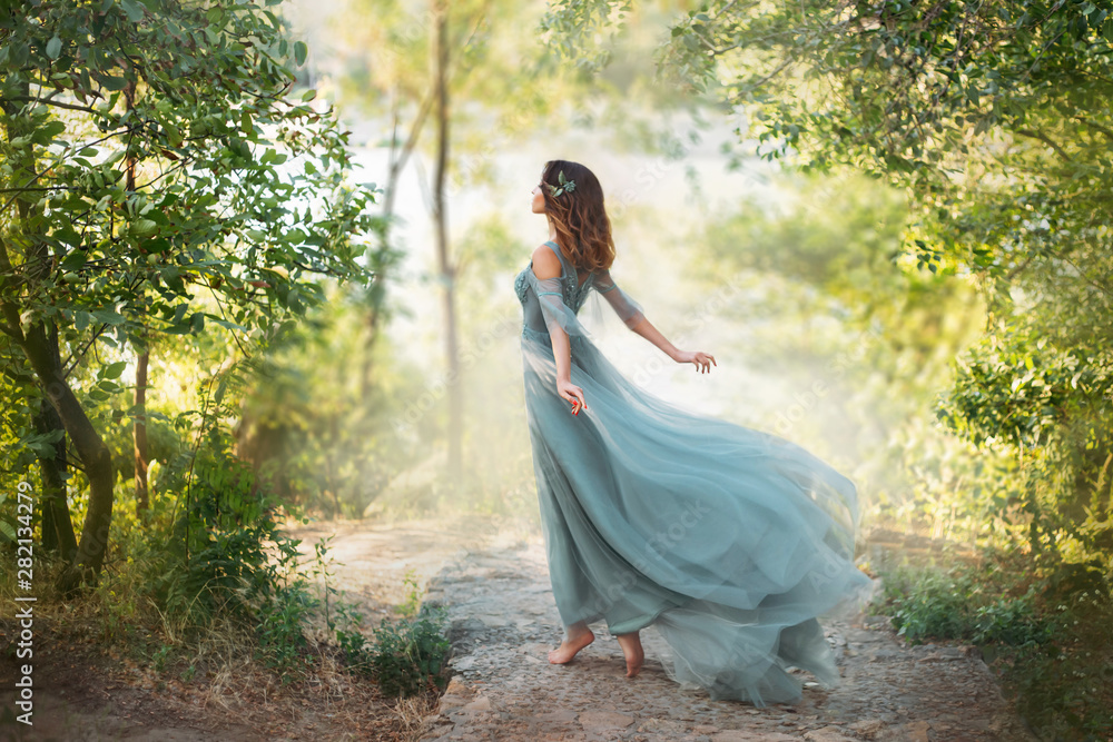 Fototapety, obrazy: fairy-tale princess in light summer blue turquoise dress on wide path and walks towards wind, graceful dancing girl in image of flower with flying long hem of dress, nymph of bright green forest