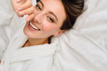 Young Gorgeous Smiling Woman With Dark Hair In White Bathrobe Dreamily Looking In Camera Lying On Bed In Hotel