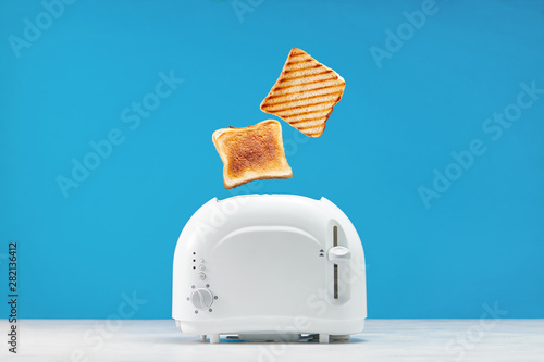 Foto Roasted toast bread popping up of toaster with blue wall