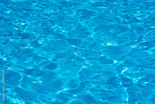 Background of water in a blue swimming pool, water surface with sun reflection