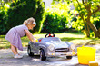 canvas print picture - Cute gorgeous toddler girl washing big old toy car in summer garden, outdoors. Happy healthy little child cleaning car with soap and water, having fun with splashing and playing with sponge.