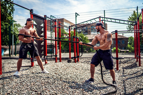 Fotografie, Obraz  Athletic man working out with rope at street gym yard