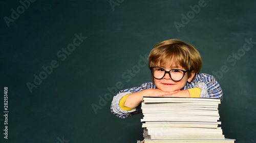 Funny little boy pointing up on blackboard. School concept. School kids against green chalkboard. Learning concept. Happy mood smiling broadly in school