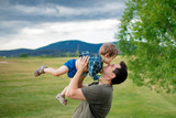 Fototapeta Panels - Father and toddler boy have a fun in a mountains