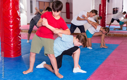 Foto auf Leinwand Logo Kids exercising self-defense movements