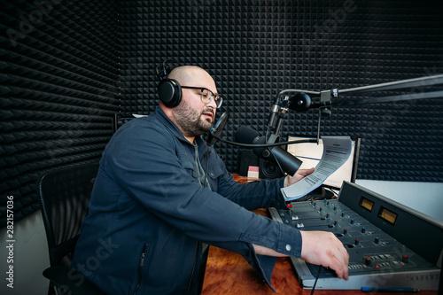 Fényképezés  Talking male radio presenter read text on paper in radio station