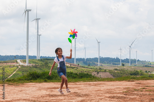 Cute asian child girl is running and playing with wind turbine toy  with fun in Fototapete