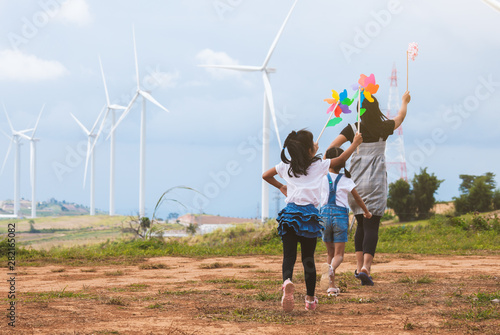 Leinwand Poster Two asian child girls and their mother are running and playing with wind turbine