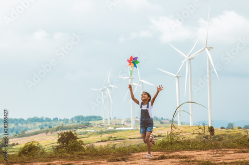 Leinwand Poster  Cute asian child girl is running and playing with wind turbine toy  with fun in