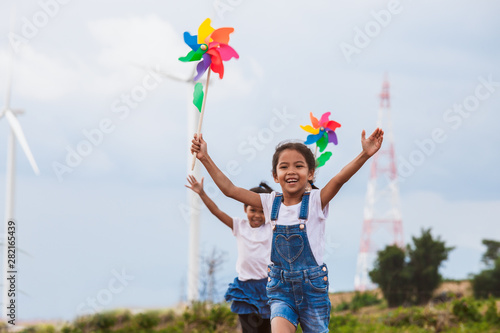 Leinwand Poster Two asian child girls are running and playing with wind turbine toy together wit