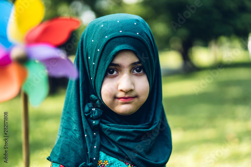 Fotografering Portrait of happy little muslim girls child with hijab dress smiling and looking