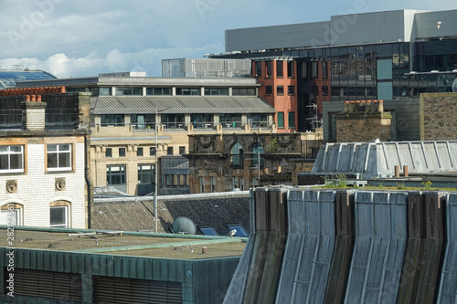 A mix of rooftop architecture styles of a Glasgow, Scotland cityscape is shown during the day in the 2010s.