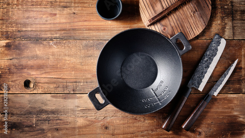 Poster de jardin Vache Set of dishes for Asian cuisine, small cast iron wok, Japanese knives on a wooden background. Top view, space for text.