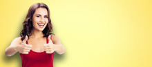 Portrait Of Young Happy Smiling Beautiful Woman In Casual Clothing, Showing Thumbs Up Gesture, Over Yellow Color Wall Background. Happy Girl In Red Dress.