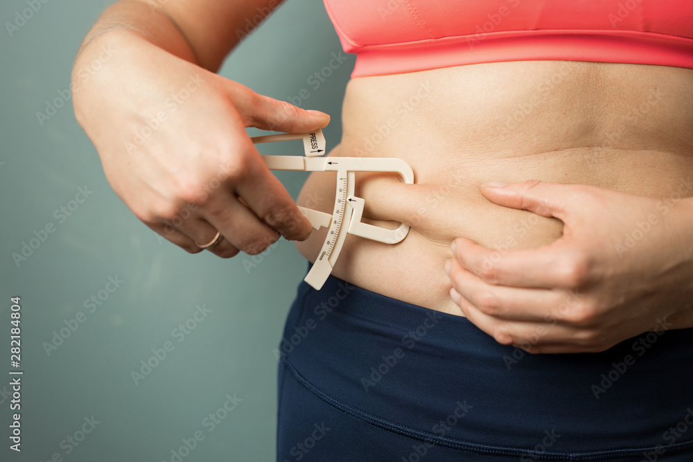 Fototapeta Woman measuring her body skin fat with fat caliper