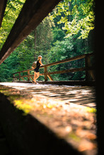 Hiking In An Idyllic Forest: Young Girl Is Standing On A Wooden Footbridge And Enjoys The View