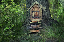 Fairytale Forest House. Little Wooden Fairy Door In Tree Trunk. Tree House In Woodland Setting, Pixie Or Elf Home. Rustic Wooden Door Built Into Foot Of Tree Trunk In Woods. Soft Selective Focus