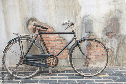 A rusty old  bicycle by the...