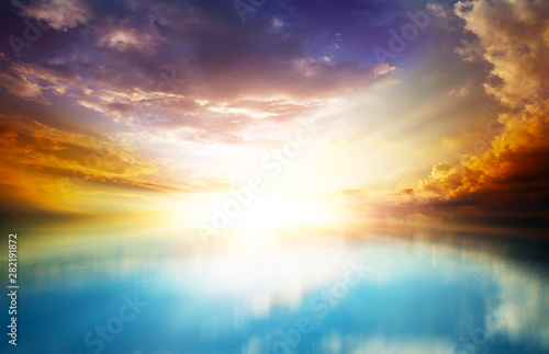 scenic sunset in the open sea with cloudy skies and bright sunlight