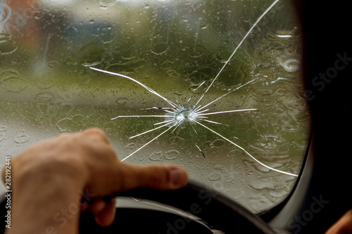 Fototapeta Broken windshield of a car. A web of radial splits, cracks on the triplex windshield. Broken car windshield, damaged glass with traces of oncoming stone on road or from bullet trace in car glass obraz