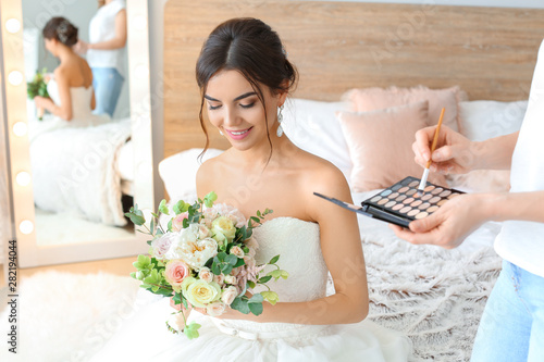 Photo Professional makeup artist working with young bride at home