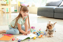 Cute Little Girl With Dog Painting While Sitting On Carpet