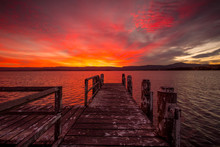 Burning Red Sunset  On The Lake With Timber Jetty