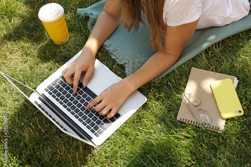 Female blogger with laptop lying on grass in park