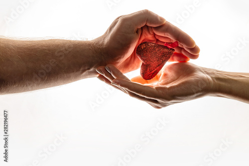 Female and male hands are keeping red heart together Canvas Print