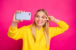 canvas print picture - Photo of pretty lady making selfies showing v-sign near eye wear yellow hoodie isolated pink background