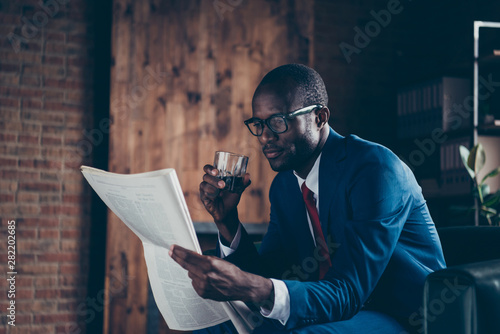 Valokuva  Photo of dark skin macho guy sitting office sofa drinking alcohol beverage readi