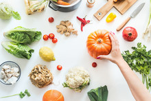 Healthy Food And Clean Seasonal Eating Concept. Various Organic Vegetables On White Desk Background With Pot , Cutting Board And Knife. Female Hand Holding Pumpkin. Vegetarian Background. Top View