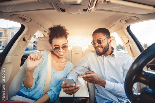 Foto  African-american couple using navigator app on phone in car