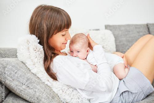Staande foto Wanddecoratie met eigen foto Mother lovingly cuddles with her baby