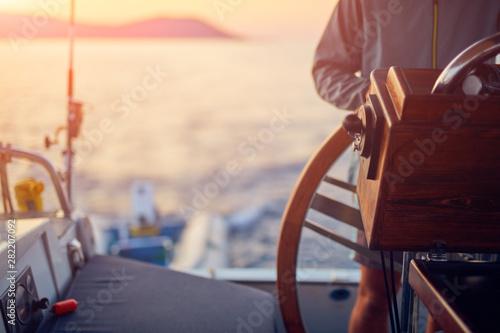 Fotografia  Sailor using wheel to steer rudder on a sailing boat.