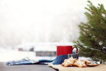 Holiday Cookies And A Mug With A Scarf Under The Tree Against The Background Of A Landscape With Snowy Houses. Cozy Winter Morning