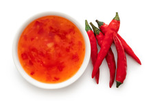 Sweet Chilli Sauce In A White Ceramic Bowl Next To A Pile Of Red Chillies Isolated On White From Above.