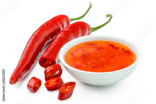 Printed kitchen splashbacks Hot chili peppers Sweet chilli sauce in a white ceramic bowl next to one whole and one cut red chilli isolated on white.