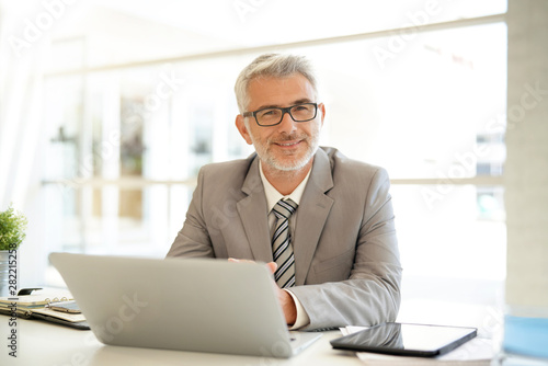 Pinturas sobre lienzo  Mature businessman sitting at desk looking at camera