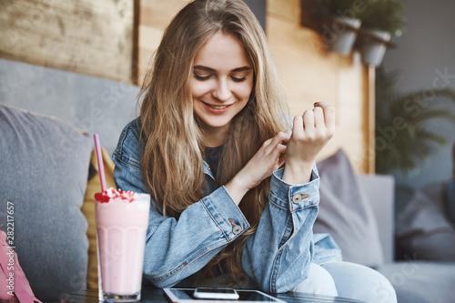 Fotografie, Obraz  Stylish european girlfriend with fair hair in denim jacket, sitting in street ca