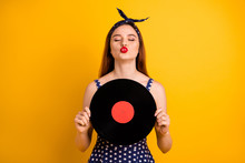 Portrait Of Her She Nice-looking Attractive Lovely Winsome Cheerful Cheery Dreamy Straight-haired Lady Holding In Hands Round Disc Sending You Kiss Isolated On Bright Vivid Shine Yellow Background