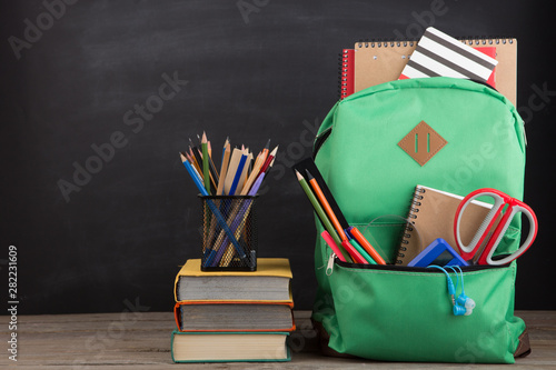 Photo sur Toile Les Textures Education concept - school backpack with books and other supplies, blackboard background