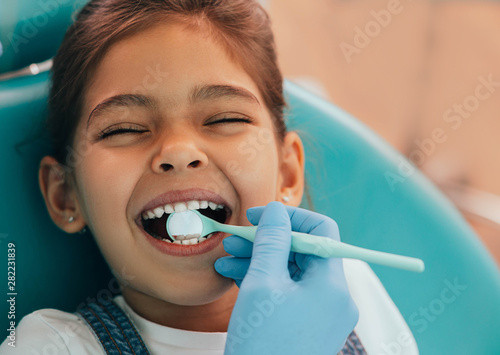 Leinwand Poster  Cute little girl getting teeth exam at dental clinic
