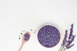 Lavender flowers in wooden plate and spoon, branches on white background, toned. Spa, recipe concept. Top view, close-up, flat lay, copy space, layout design