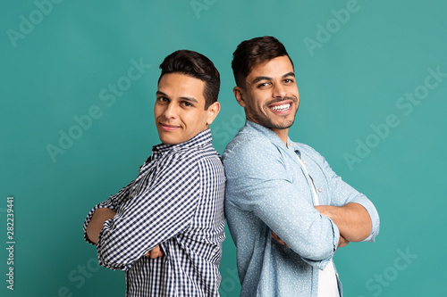 Photo Two Latin Guys Standing Back-To-Back On Turquoise Studio Background