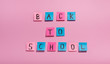 Back to school text of colored stickers on pink background