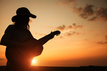 Silhouette Of Young Woman Playing Guitar At Sunset
