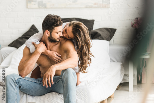 Stampa su Tela selective focus of two people in love hugging while sitting in bed