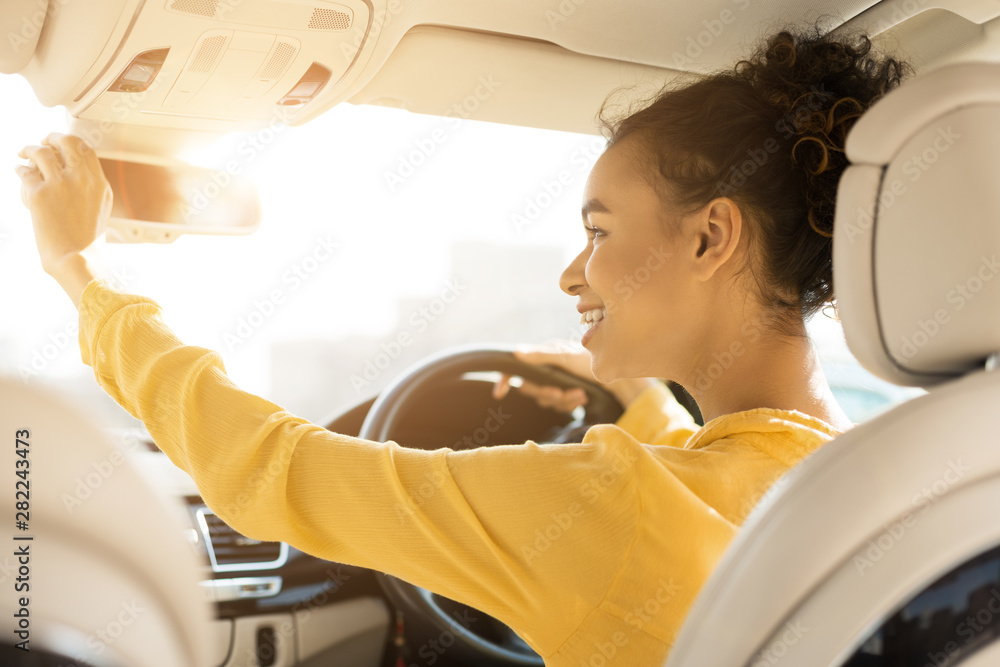 Fotografía  Happy girl touching rear view mirror, driving car